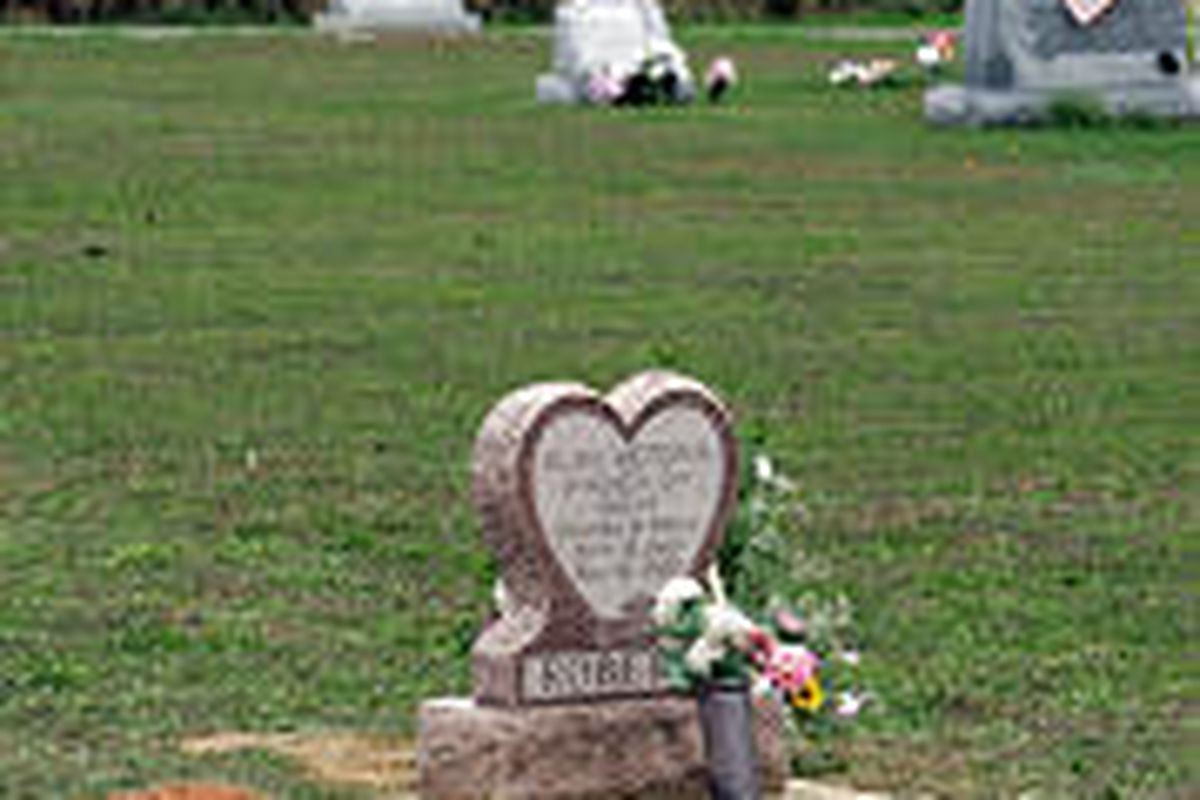 The grave site of Charles Carl Roberts IV is shown next to the memorial for his daughter, Elise Victoria, Saturday.