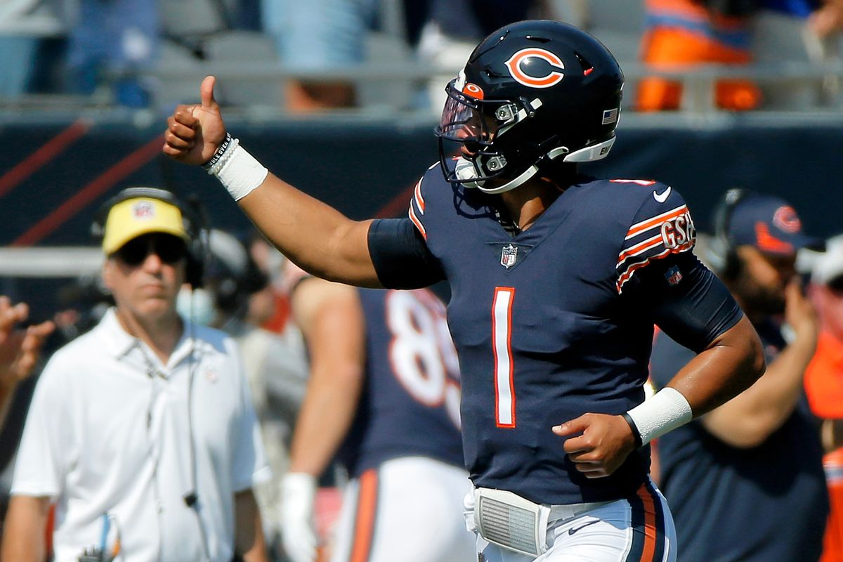 Chicago Bears quarterback Justin Fields (1) gives a thumbs up to fans as he runs on the field before the game against the Cincinnati Bengals at Soldier Field.