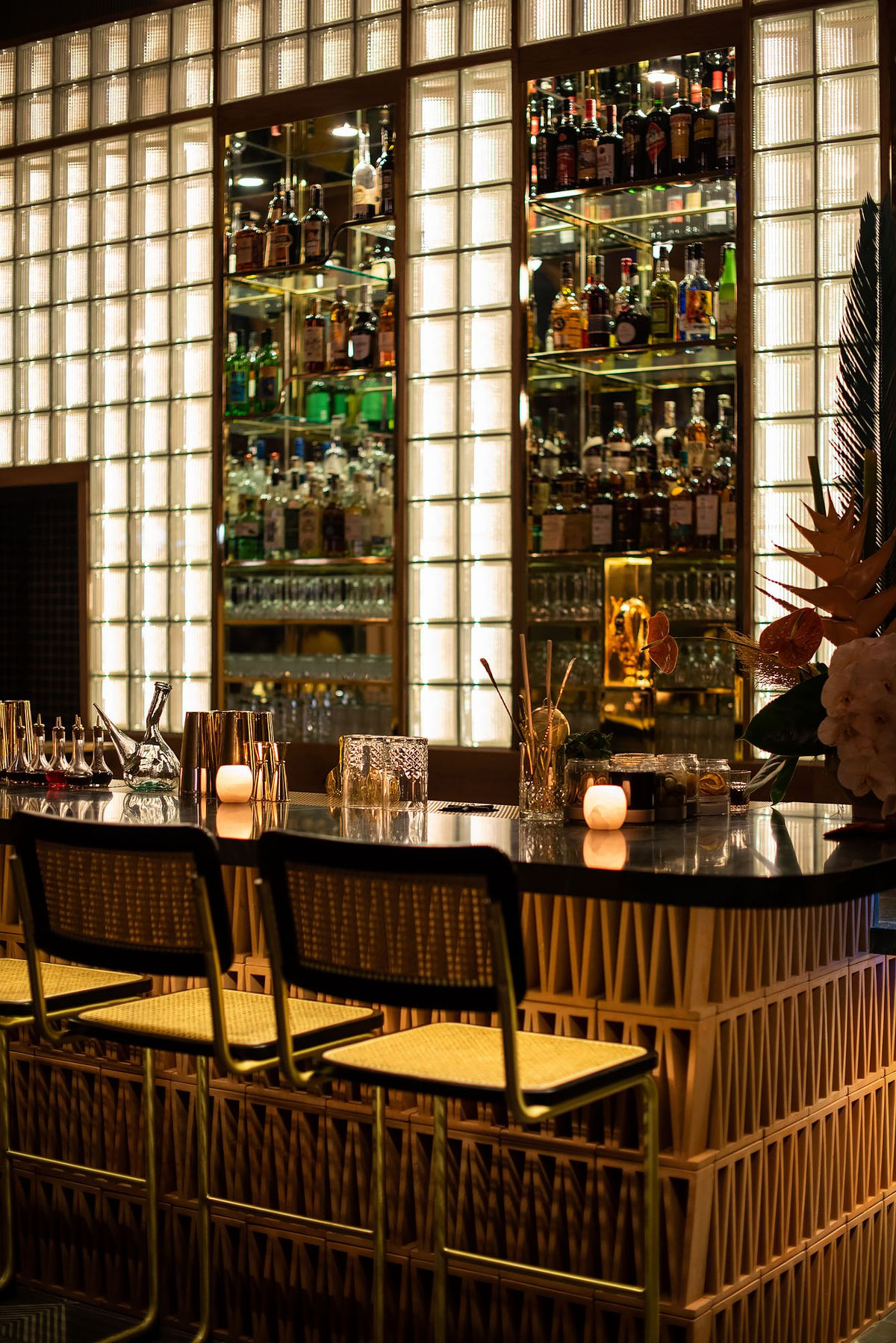 A back bar set in with glass blocks and wicker chairs.