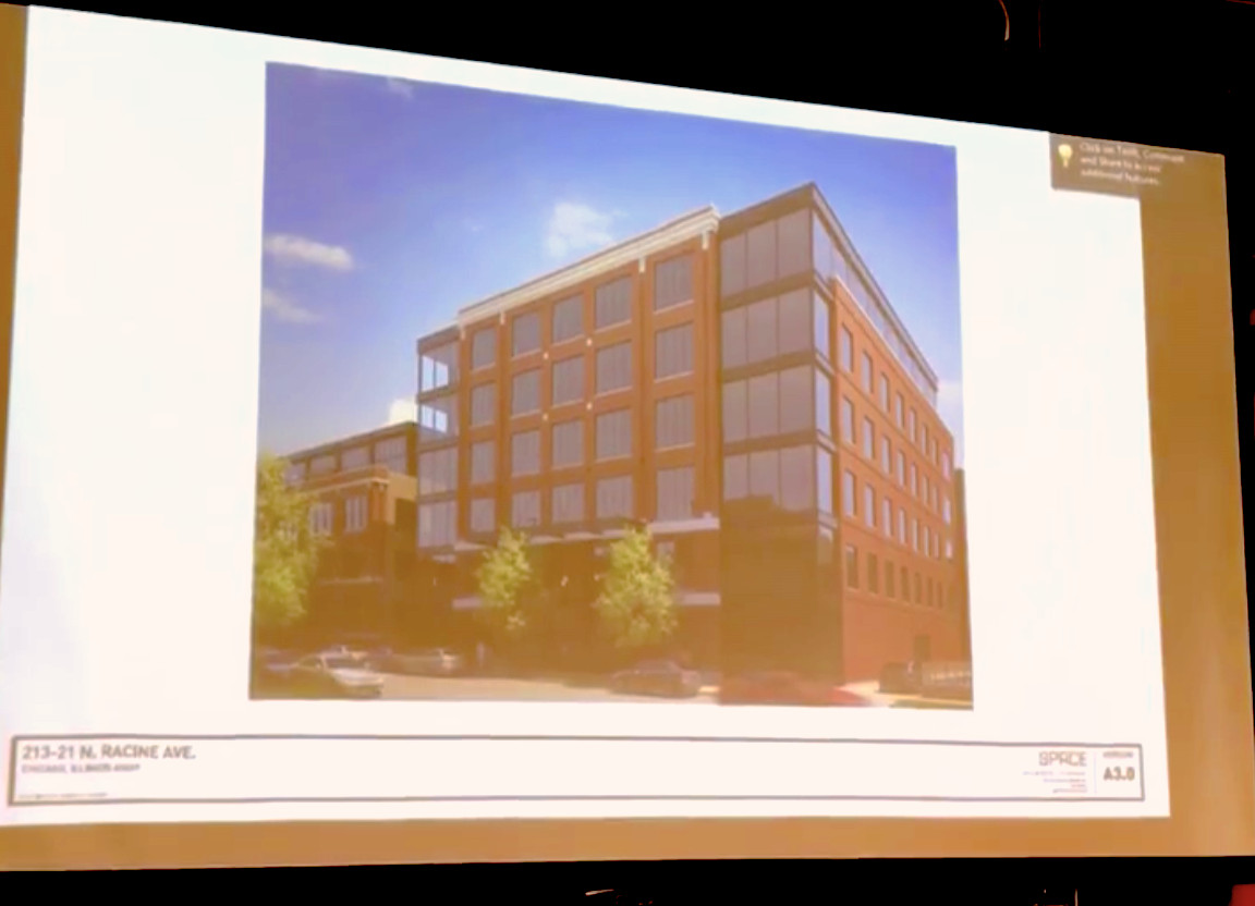 A presentation slide showing a six-story building with a brick facade and all-glass corners. There are trees on the sidewalk in front.