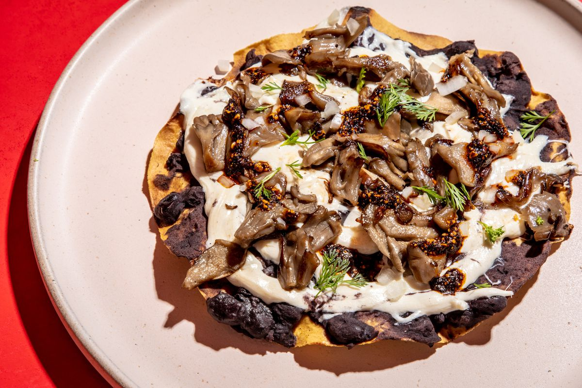 Piles of maitake mushrooms and white Oaxacan cheese sit above a layer of black beans on a burnished corn tlayuda