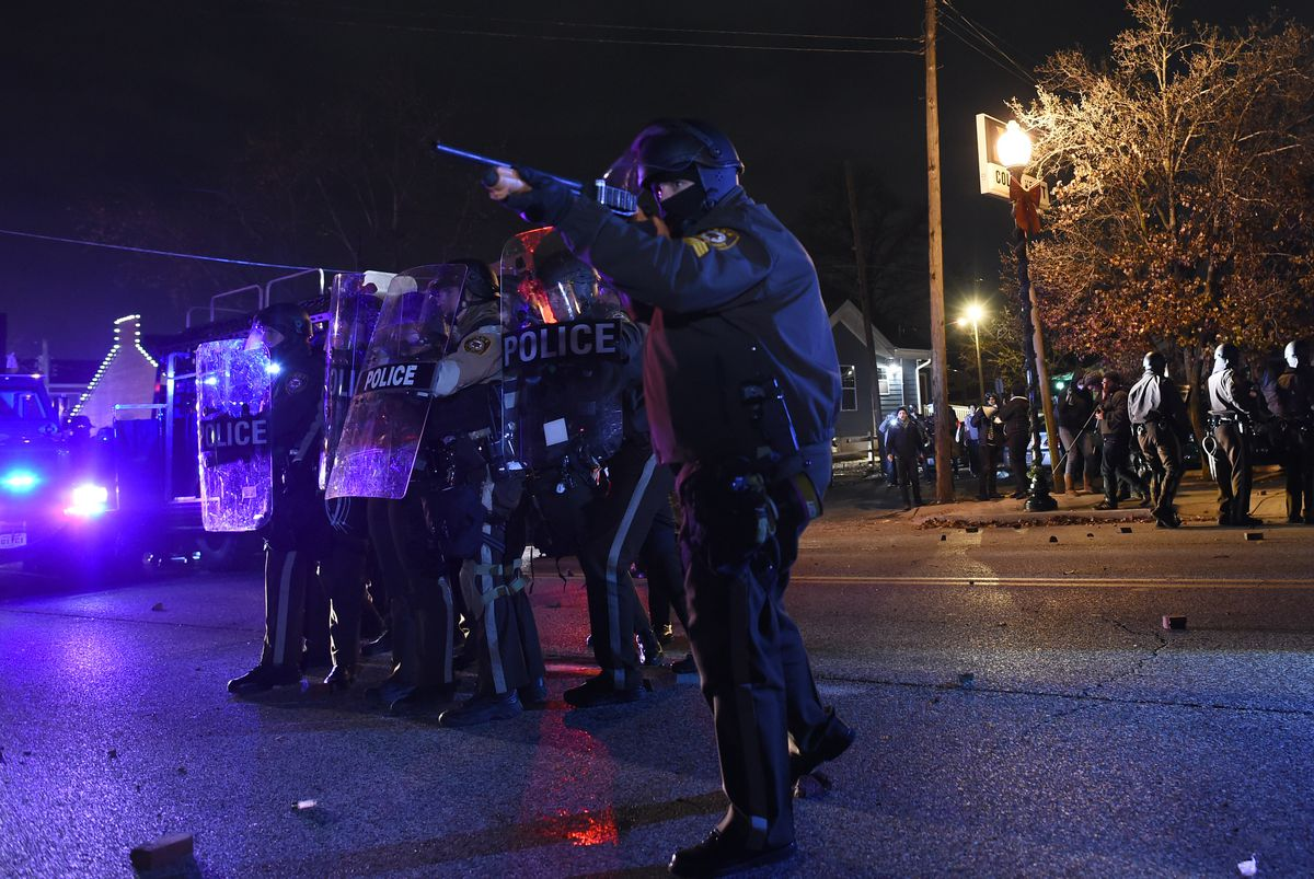 An officer aims his rifle at protesters in Ferguson, Missouri, in November 2014.
