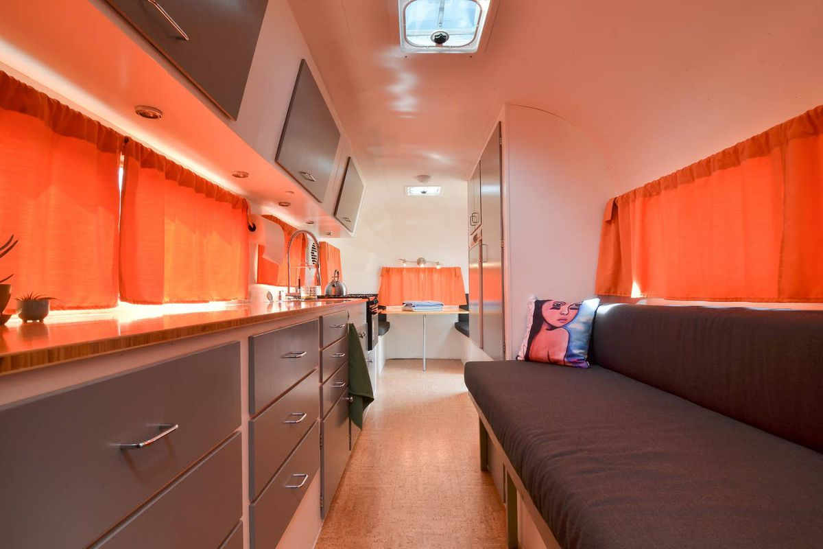 A narrow corridor with a built-in couch along the right wall and a countertop above gray cabinetry along the left. There's a skylight and orange curtains over windows on either side and ahead.