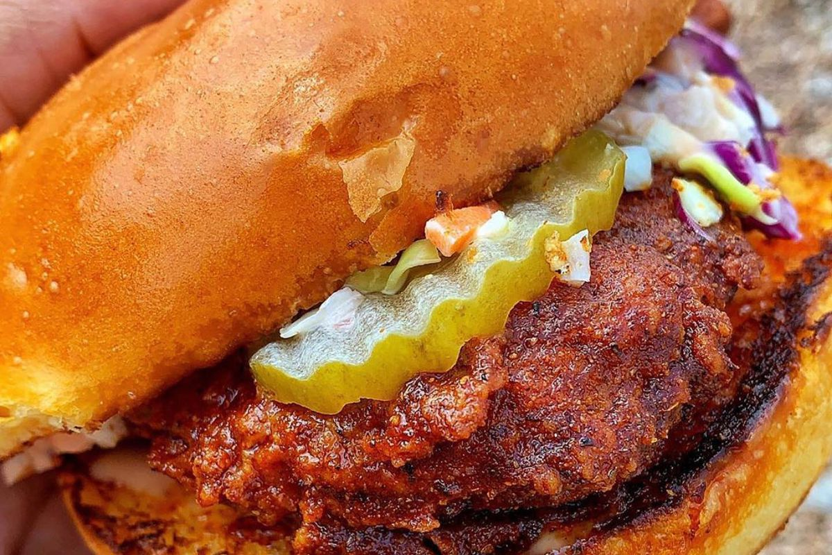 A spicy chicken sandwich with pickles and slaw