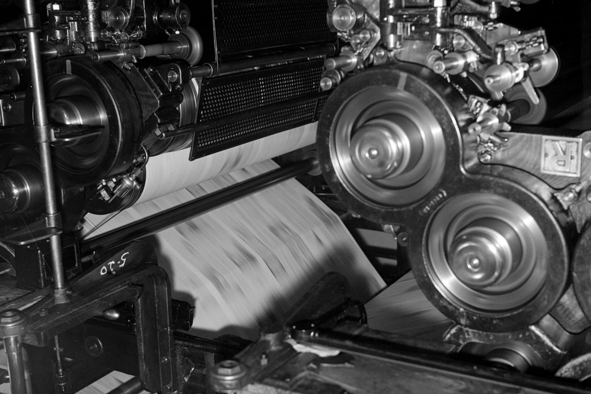 A 1937 black-and-white photograph of a newspaper being printed on a printing press.