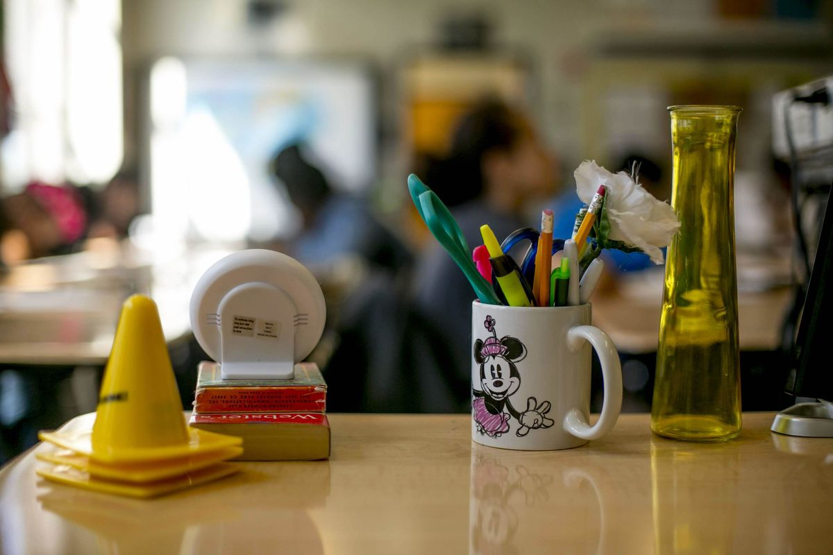 Markers, pencils and pens in a Minnie Mouse coffee cup, small yellow cones, a dictionary, and other items sit atop a desk in a classroom.
