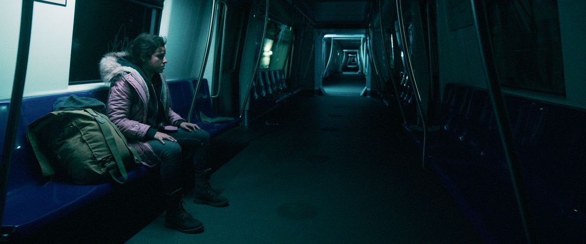 Cristina Rodlo as Ambar sits in a subway train that seems to extend to infinity in No One Gets Out Alive