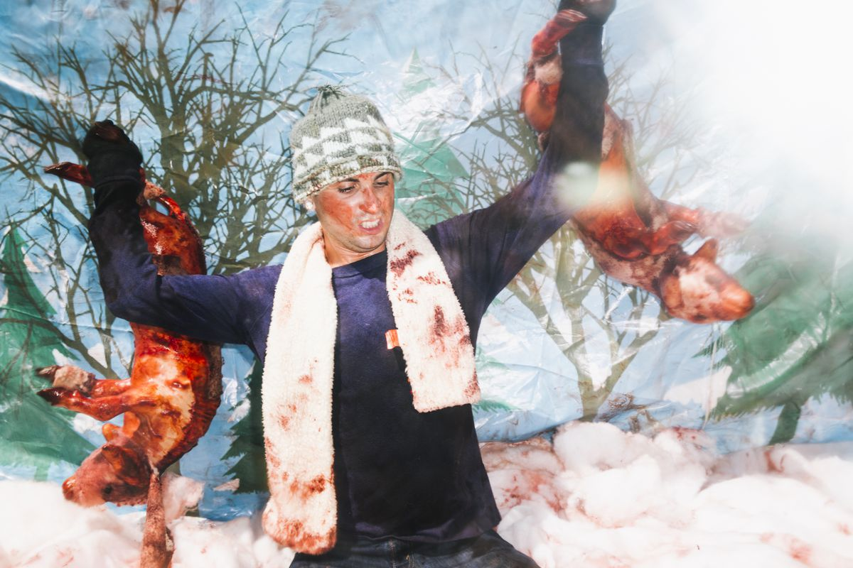 PETA employee Christopher Merrow holds two fake bloody sheep inside a giant snow globe at a wool protest in Los Angeles.