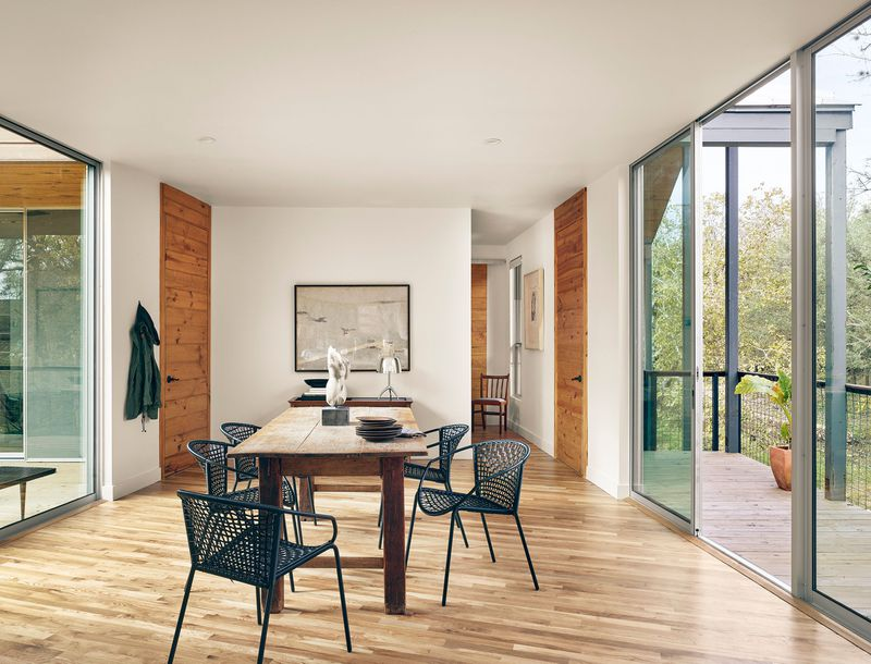 A dining room with wood floors and openings to a deck.
