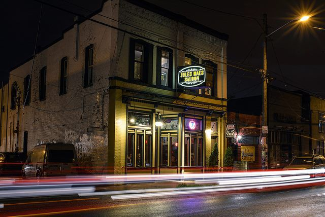 The front of Jules Maes Saloon in Georgetown, with the sign lit up at night