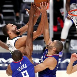 Utah Jazz center Rudy Gobert (27) fights to get the ball up with LA Clippers forward Serge Ibaka (9) and LA Clippers forward Nicolas Batum (33) defending as the Utah Jazz and LA Clippers play in an NBA basketball game at Vivint Smart Home Arena in Salt Lake City on Friday, Jan. 1, 2021. Utah won 106-100,