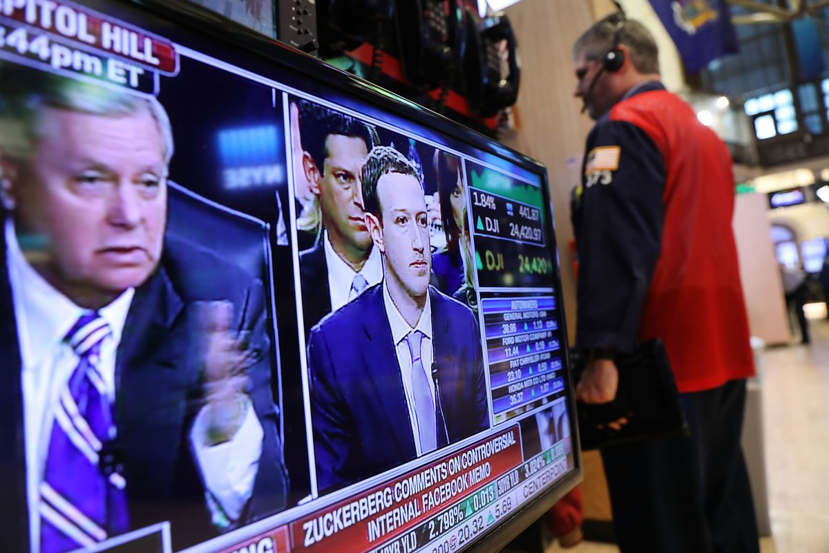 A television on the floor of the New York Stock Exchange displays a live feed of Facebook CEO Mark Zuckerberg as he testifies before Congress.