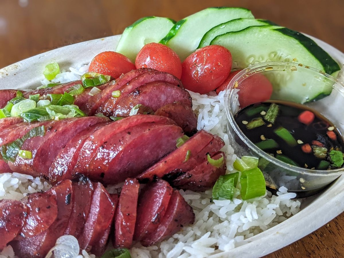 Slices of bright red Chinese-style sausage sit on a bed of white rice, with cherry tomatoes and sliced cucumbers garnishing the dish. There's also a plastic cup of a thin, dark brown dipping sauce.