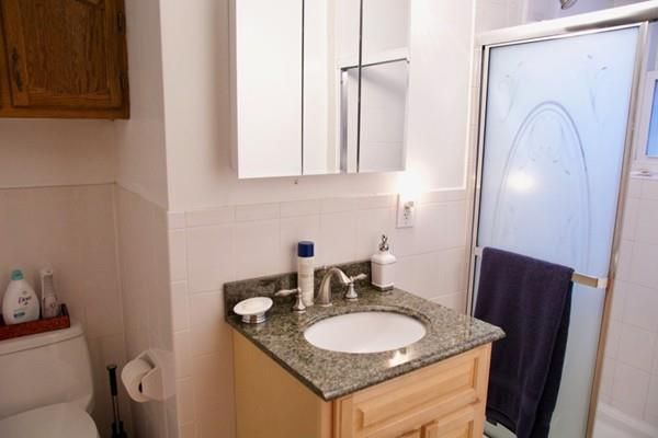 A small bathroom with a sink next to a shower with sliding plastic door.