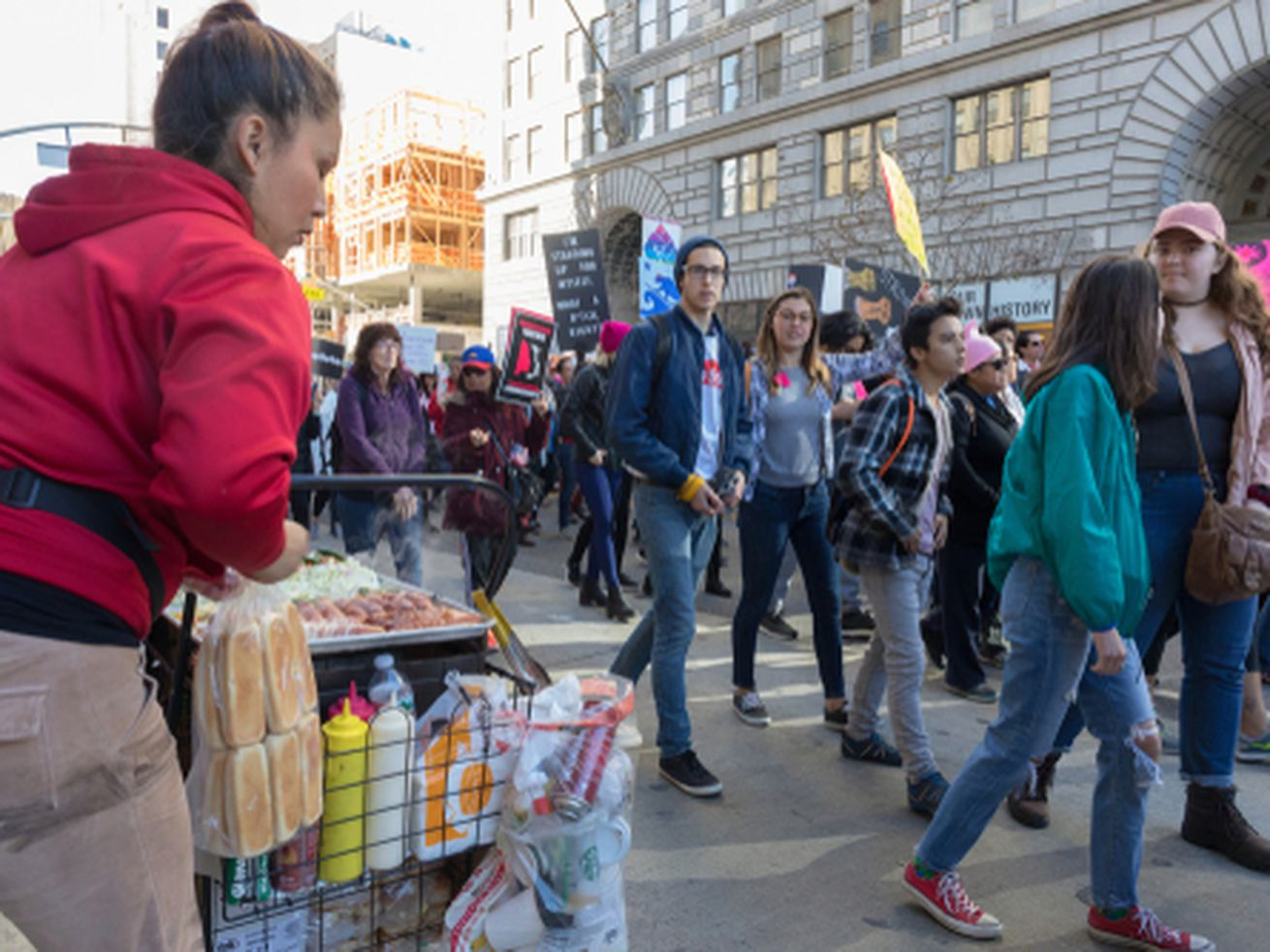 2nd Annual Women's March marchers passing by a street food vendor along the march route