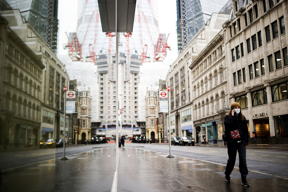 A person holds a phone to their ear as they walk along a mostly deserted street in downtown London.