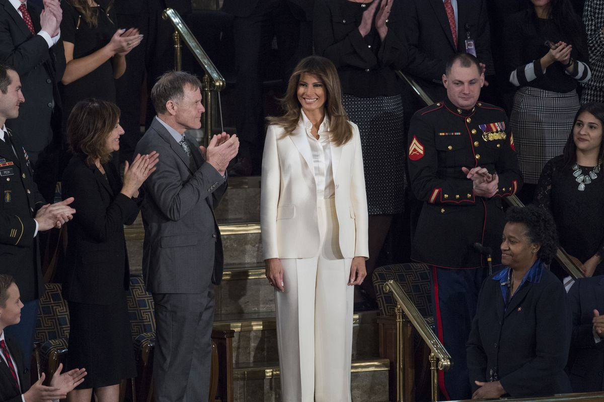 Melania Trump stands while the crowd applauds her.