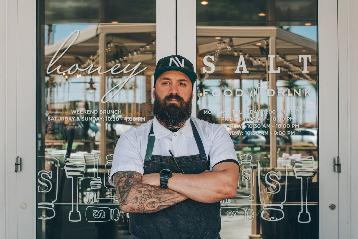 A chef stands with his arms crossed in front of a restaurant