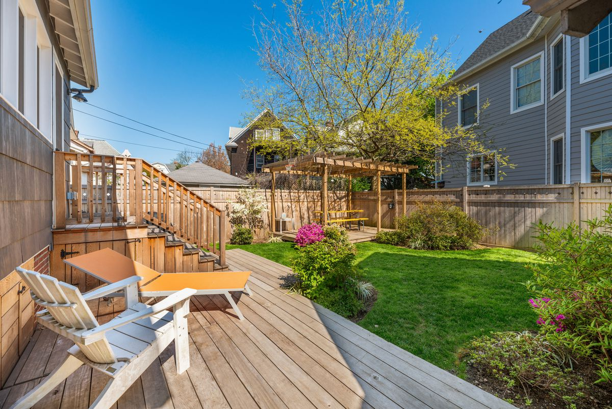 A landscaped backyard with wood fencing and several seating areas.