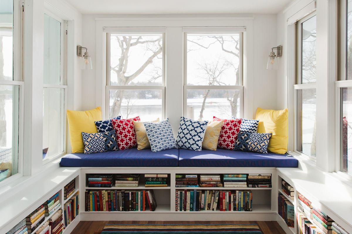 Sunroom reading nook with book storage.