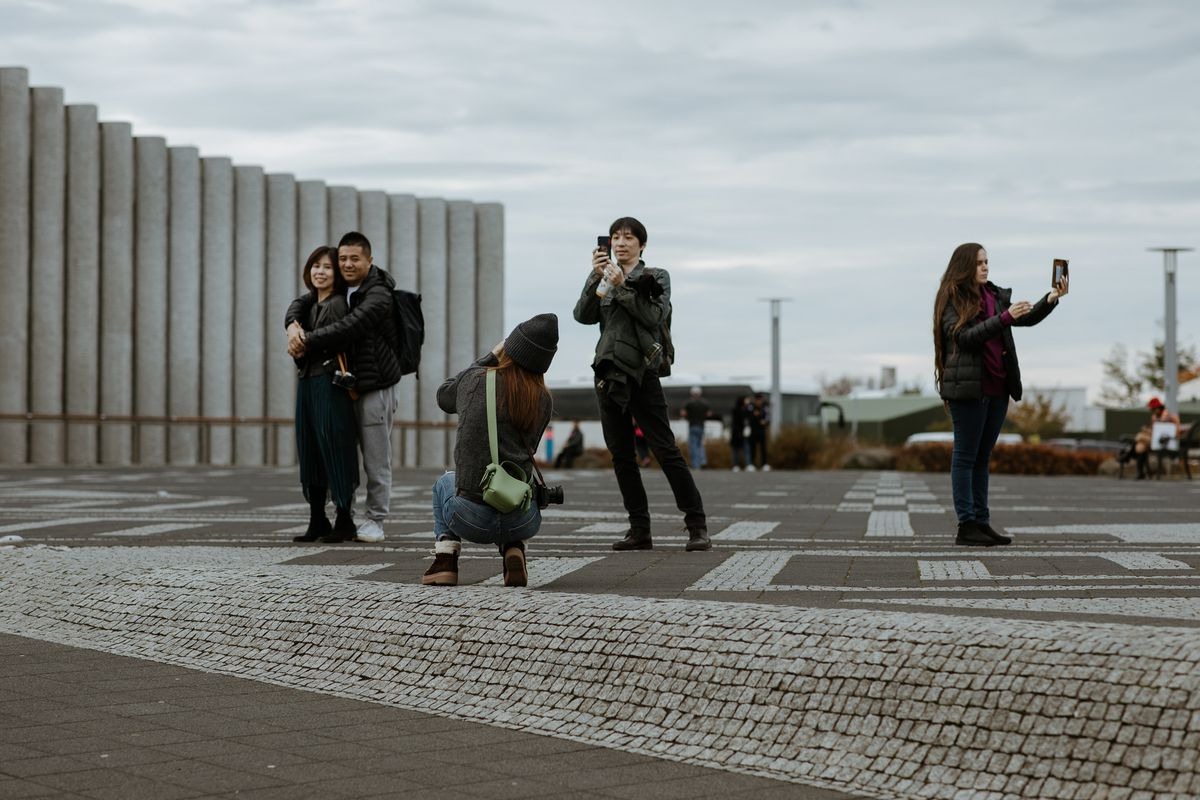 Tourists taking pictures of themselves and others at Hallgrimskirkja church.