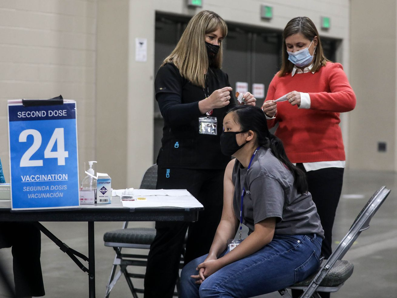 Abby Laver, bottom right, goes through a vaccination checklist while public health nurse Lee Cherie Booth, top left, and Salt Lake County Mayor Jenny Wilson, top right, open Band-Aids at COVID-19 vaccination site at Mountain America Expo Center in Sandy on Monday, April 26, 2021.