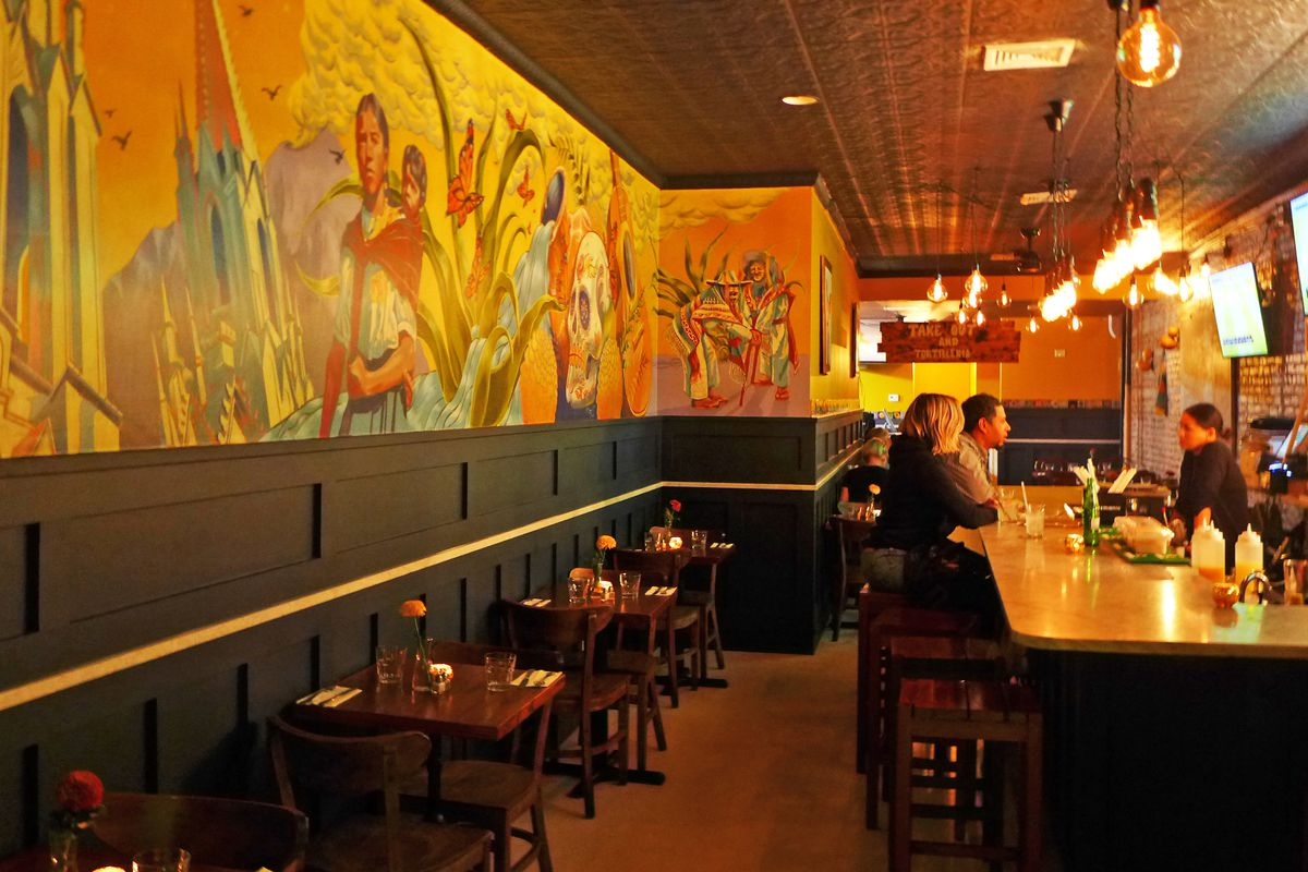 A bar on the right, a colorful Mexican mural on the left with a row of tables beneath it.