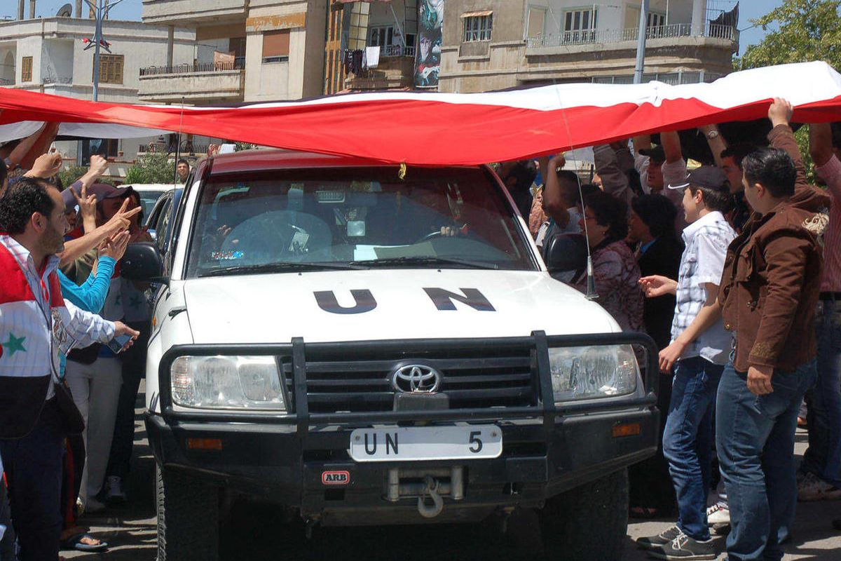 In this photo released by the Syrian official news agency SANA, a UN observers vehicle passes under a huge Syrian flag held by Syrian President Bashar Assad supporters during their visit to the pro-Syrian regime neighborhoods, in Homs province, central Sy