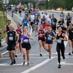 People competing in the Deseret News 10K run down Wakara Way in Salt Lake City on Friday, July 23, 2021.