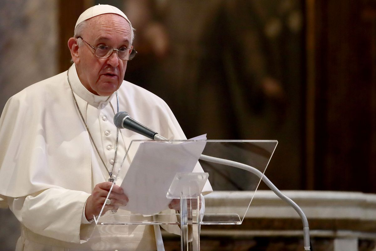 Pope Francis speaking at a podium.