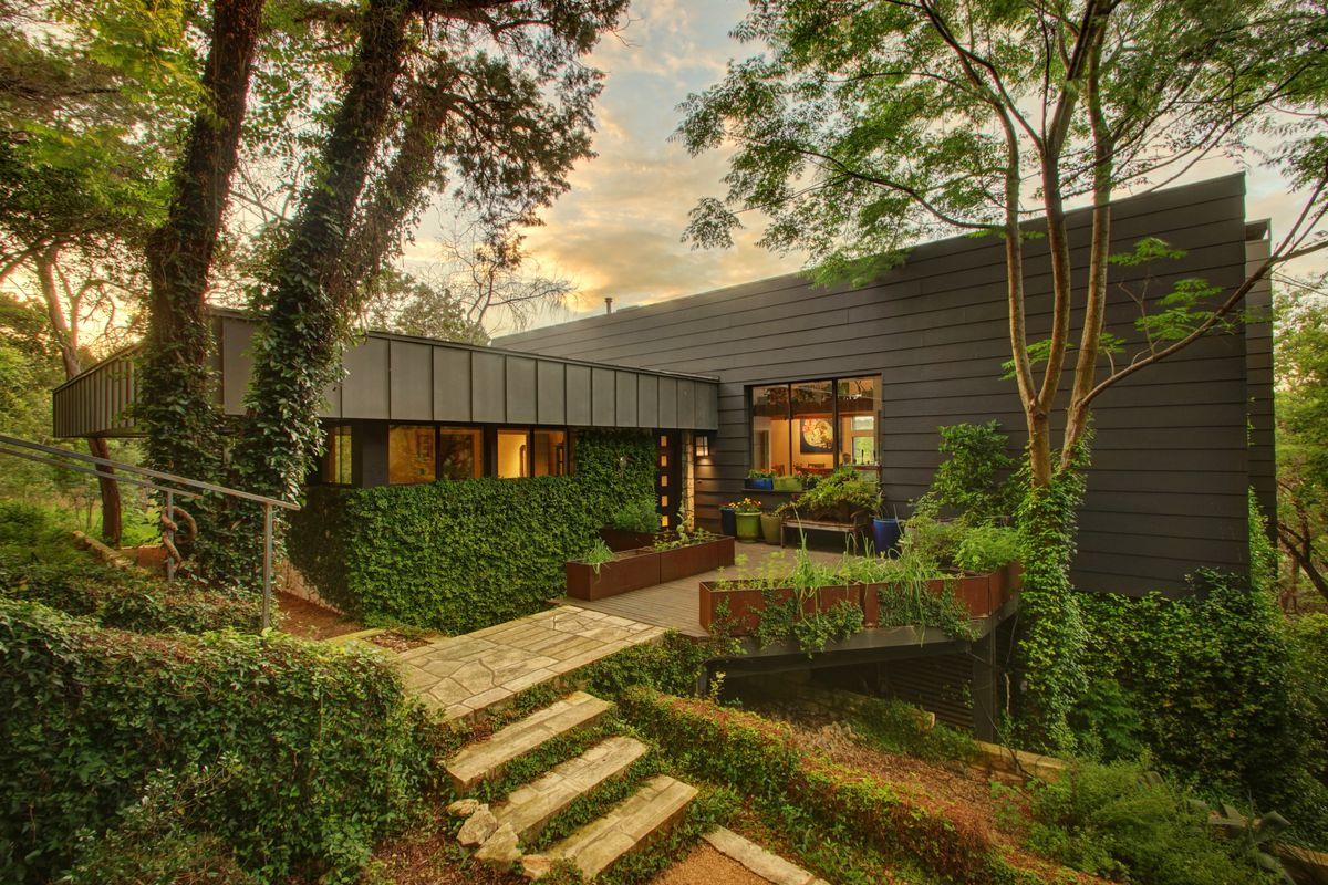 1992 boxy gray-brown metal one-story house with big patio, surrounded by very green forest