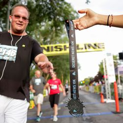 Gary Fotheringham collects a medal as he finishes the Deseret News 10K at Liberty Park in Salt Lake City on Friday, July 23, 2021.