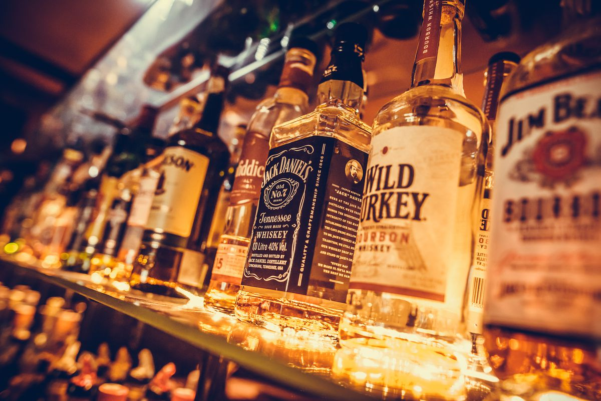 Editorial image of some alcohol bottles in a row, displayed in a pub or restaurant.