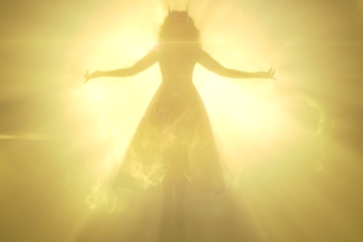 Scarlet Witch in her original costume descends from the light of the Mind Stone in WandaVision