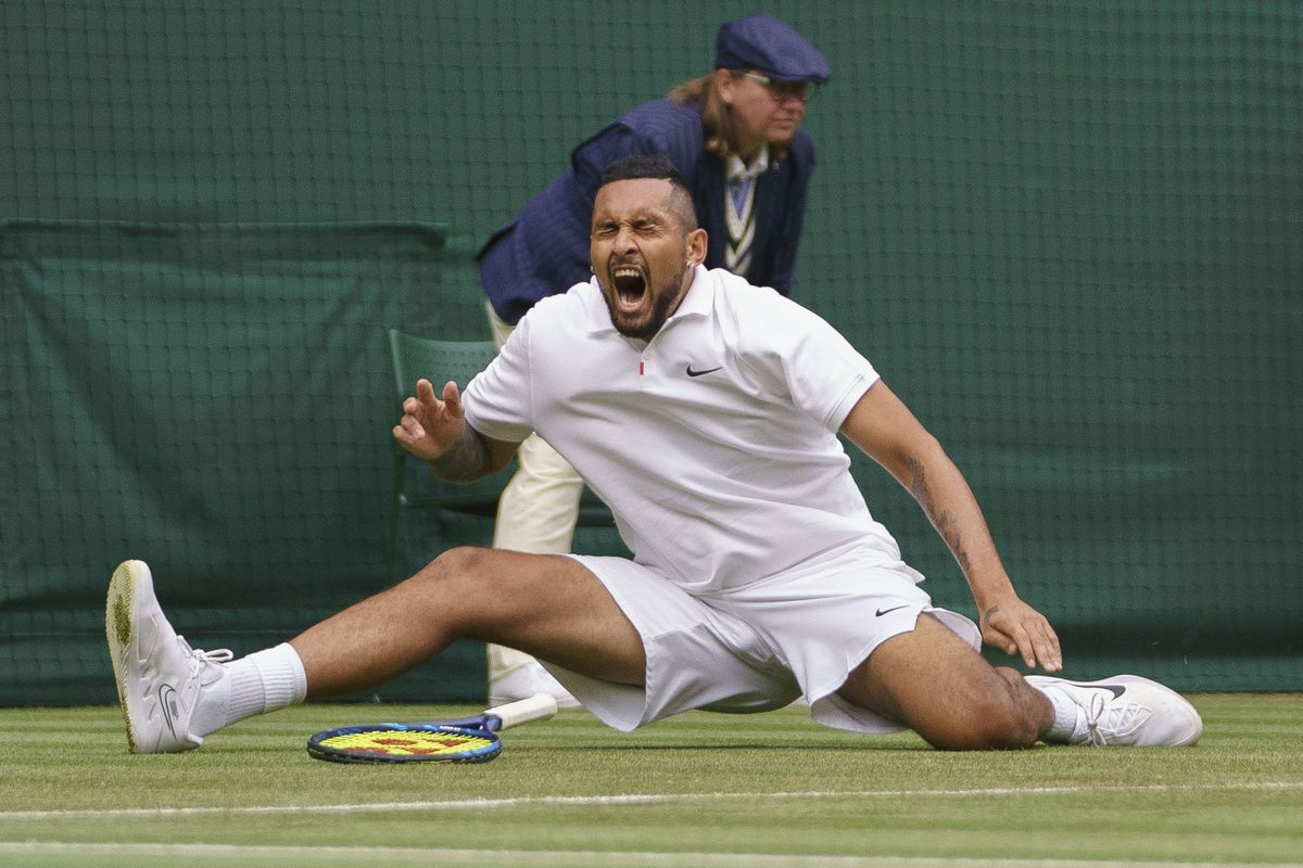 Nick Kyrgios slips after playing a return to Ugo Humbert during a first-round match at Wimbledon.