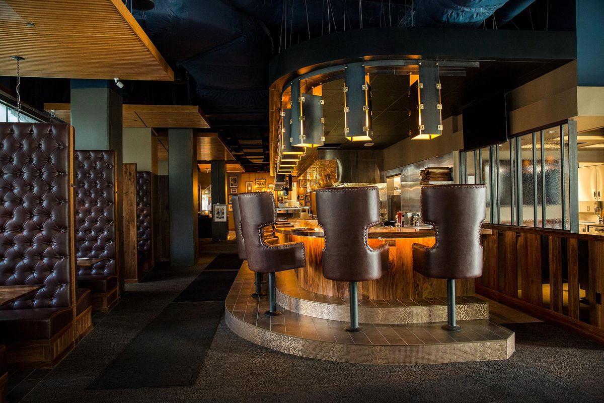 The dining room at 13 Coins, with dark leather upholstered bar stools and booths.