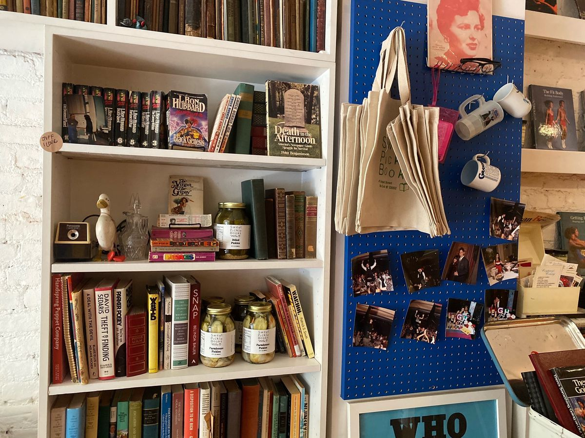 Bookshelves filled with books and pickle jars, plus a blue wall with hooks where mugs and totes are hanging for sale