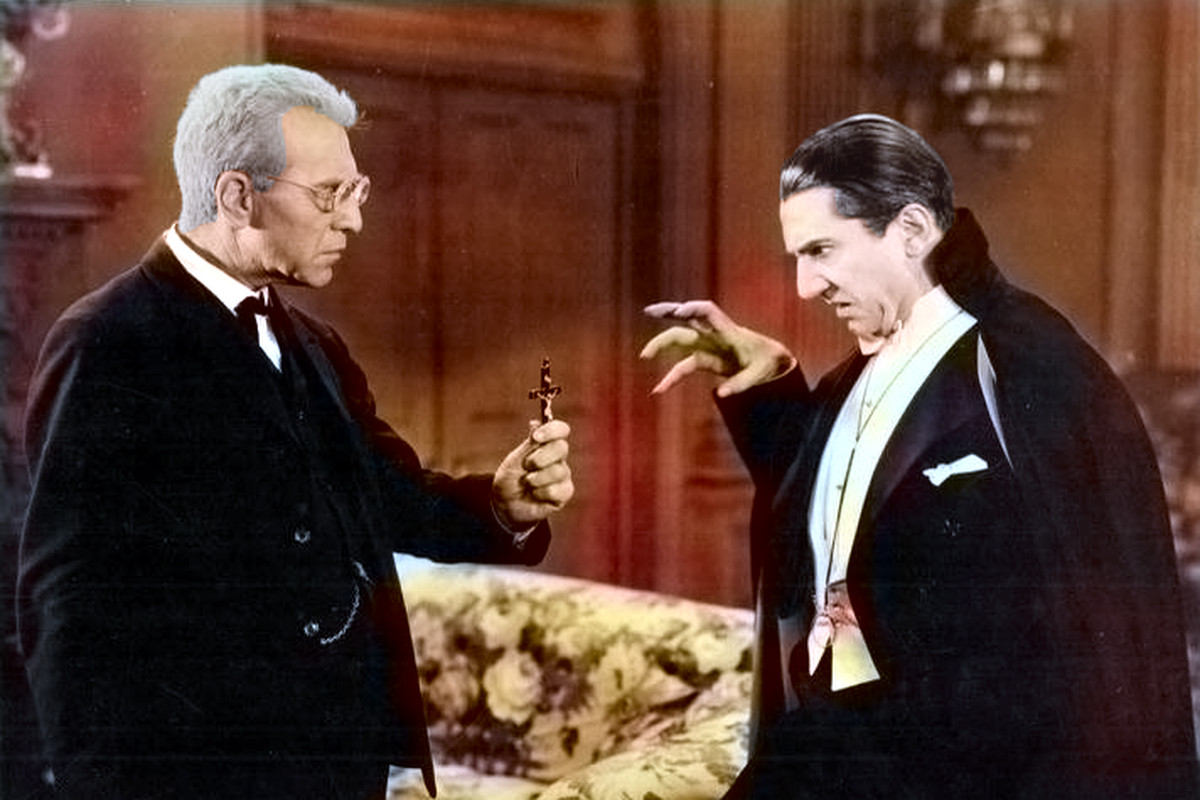 A man holds up a cross to a recoiling Count Dracula.