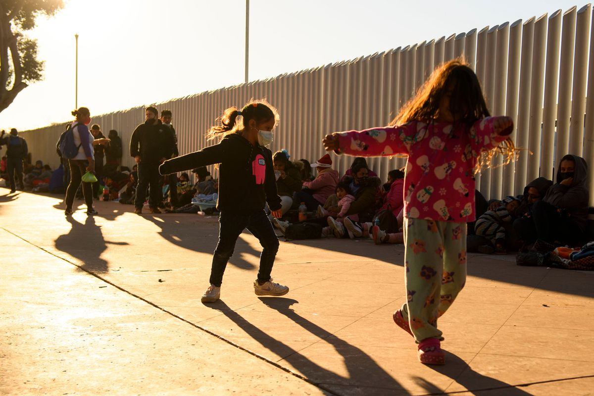 Two children, one with their hair covering their face, and the other with their face obscured by the golden light of the setting sun, appear to dance . Behind them, a line of people sit with their backs against tall metal slats of border fencing.
