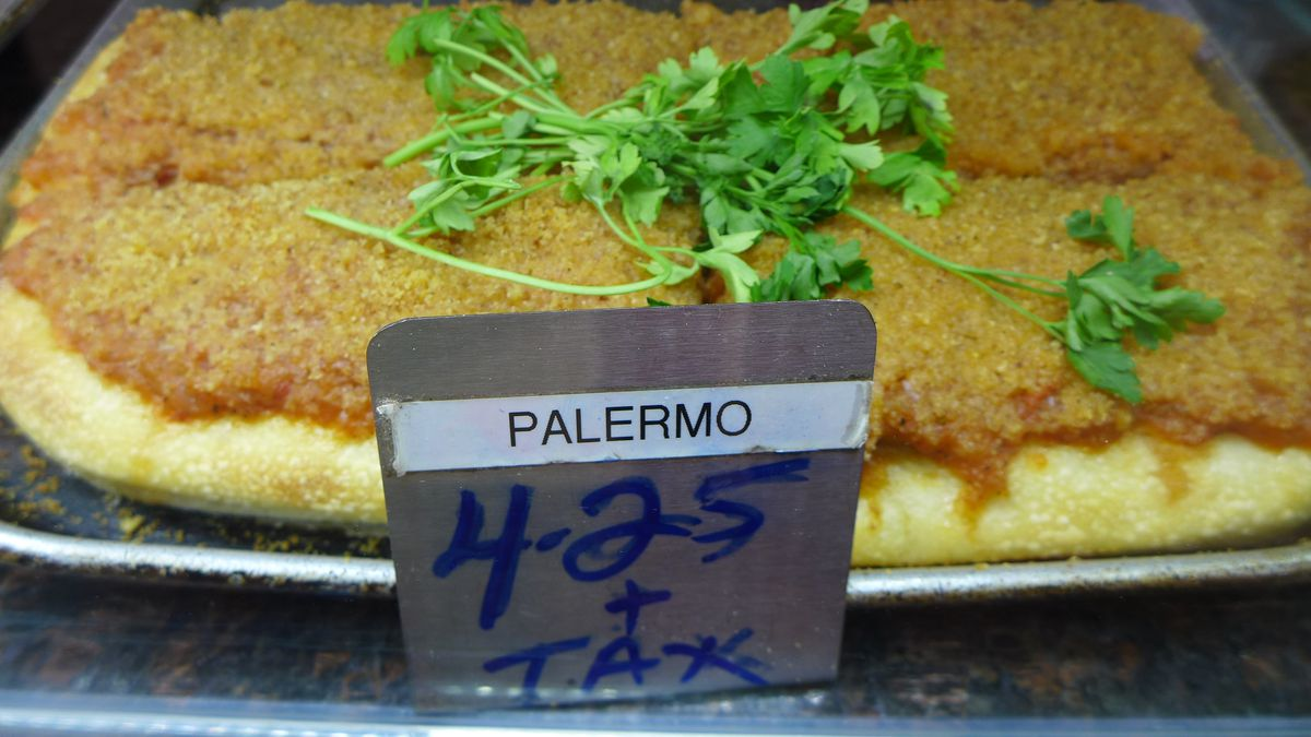 A square pan with rectangular brown slices topped with crumbs.