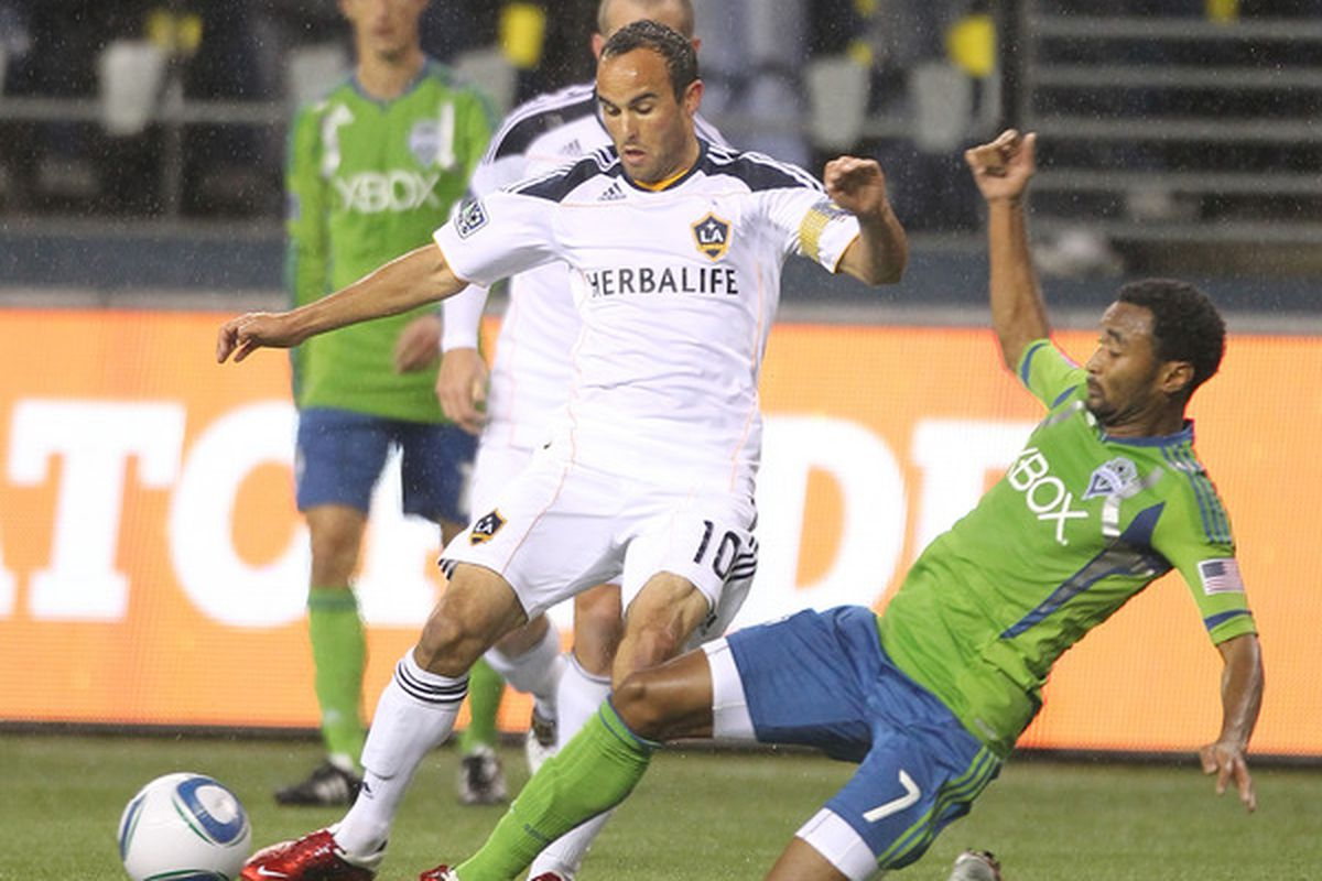 SEATTLE - MARCH 15:  Landon Donovan #10 of the Los Angeles Galaxy dribbles against James Riley #7 of the Seattle Sounders FC at Qwest Field on March 15, 2011 in Seattle, Washington. (Photo by Otto Greule Jr/Getty Images)