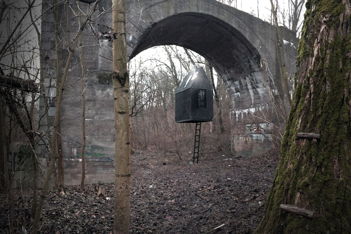 A simple, gable-roofed structure clad in black wood is suspended by steel cables underneath an old stone railway arch. The day is overcast and the trees bare.