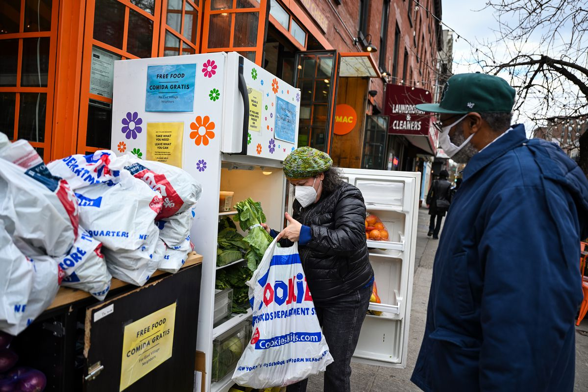 A visitor fills a plastic bag with produce for a pedestrian walking past the East Village community fridge, Dec. 4, 2020.