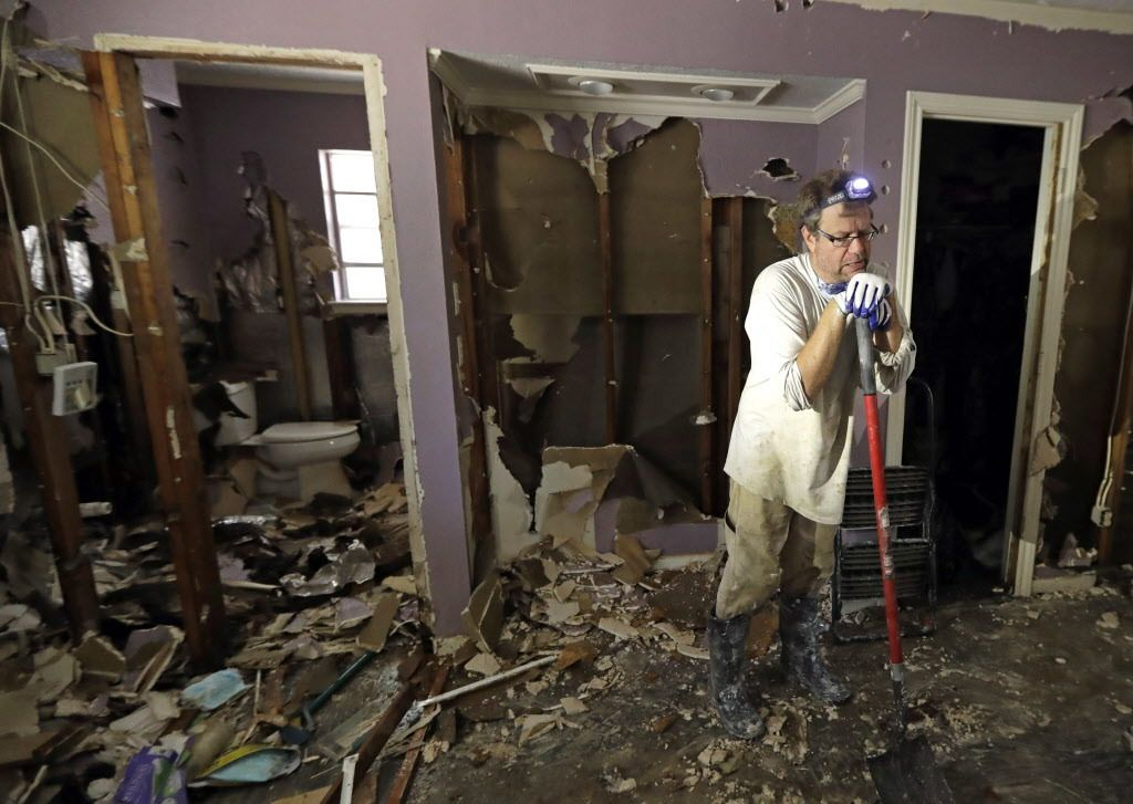 Edward Woods takes a break from cleaning up his mother's home, which was destroyed by floodwaters in the aftermath of Hurricane Harvey, on Sunday, Sept. 3, 2017, in Spring, Texas.   David J. Phillip/AP
