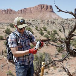 Nick Proctor signs and replaces a notice of location under a soda can located at one of his claim posts in the Colt Mesa area of the former Grand Staircase-Escalante National Monument on Friday, May 14, 2021. The Proctors are required to maintain the active status of their claims and fill out notice of location forms at their claim posts.