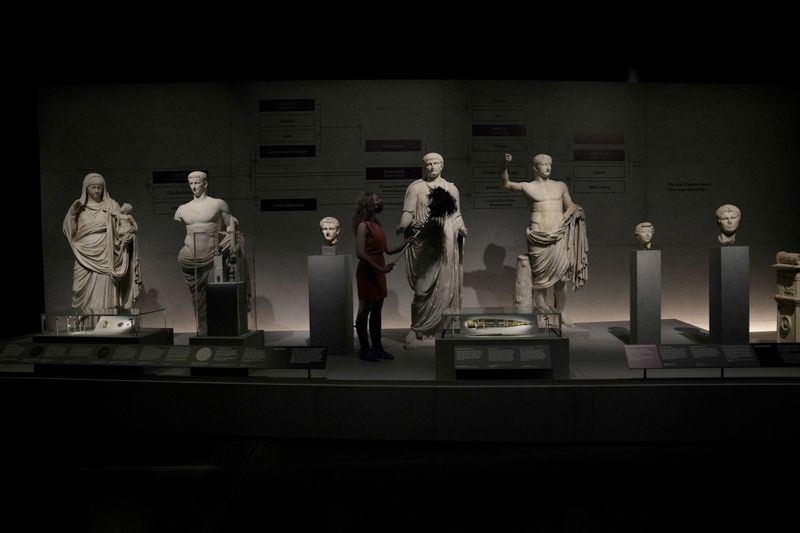 """A museum employee attends to statues of members of the Julio-Claudian family, which was from the first Roman emperor Augustus descending to Nero, the last in the line, featured in """"Nero: The Man Behind the Myth"""" exhibition, at the British Museum in London."""