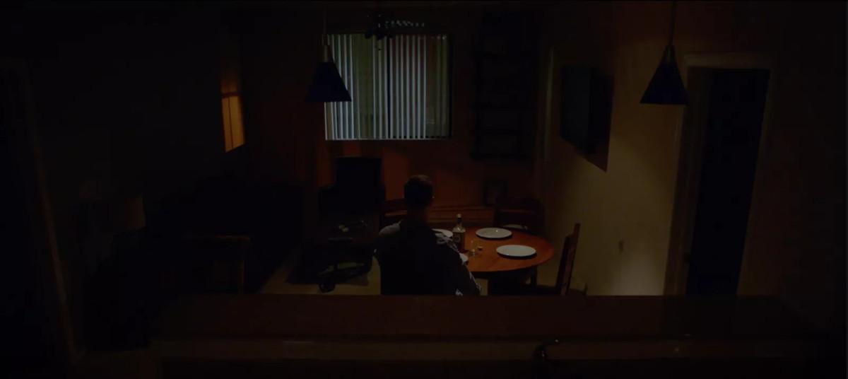 Still of Bobby eating dinner alone in the dark