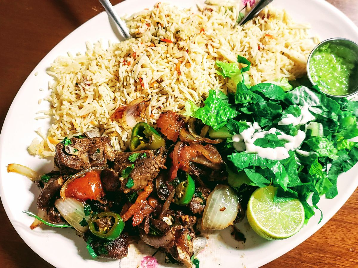 A plate of Somalian food with rice, meat, and a side salad.