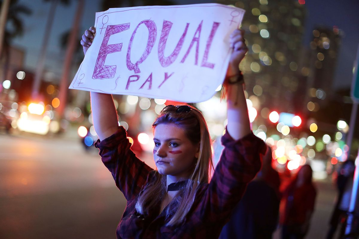 """A protester supporting equal pay at """"A Day Without a Woman"""" demonstration on March 8, 2017 in Miami"""