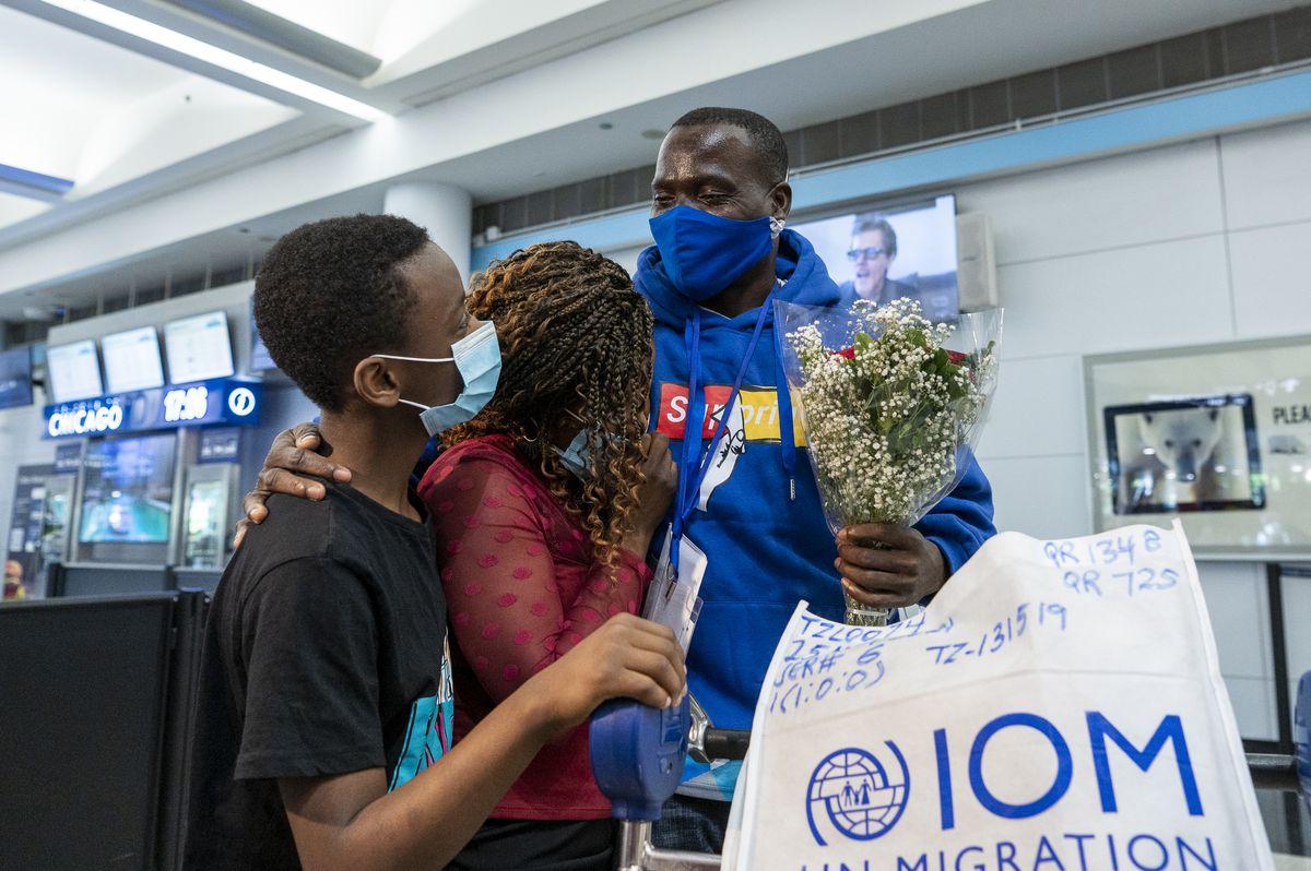 Mwenebatu Mwenemkaba, right, stands with his wife Mapenzi Mweniake and Mussa Mrisho, at O'Hare International Airport's Terminal 5, Wednesday.